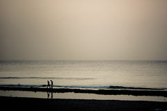 Two people in sunset on the ocean Royalty Free Stock Photos