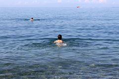 Man swims in the sea. Two people swim in the sea and the boat on the horizon Royalty Free Stock Photography