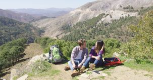 Two people taking rest while hiking. Two young people talking while having rest on summit of mountain with backpack lying around stock footage