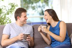 Two people talking and laughing at home. Two people talking and laughing loud sitting on a sofa at home Stock Image