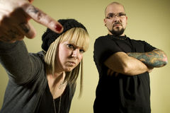 Two people with tattoos looking tough. Portrait of two people with tattoos looking tough Stock Photography