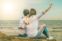 Two people with their backs to the sea. Dressed in white and casual. Feeling of joy. And peace stock images