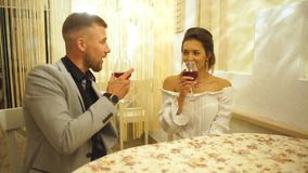 Two people toasting with wine glasses. young couple drinking red wine at restaurant. Beautiful young couple with glasses of red wine in luxury restaurant,happy stock video
