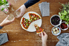 Two people toasting with wine one person eating pizza.  Stock Photo
