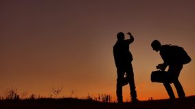 Two people tourists call for help silhouettes of the sunrise. Danger two people boy and man tourists wave their hands. Two people tourists call help silhouettes stock footage