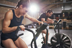 Two people training in effort on simulators. Man and women in sportswear riding in effort cycling machines in modern light gym royalty free stock images