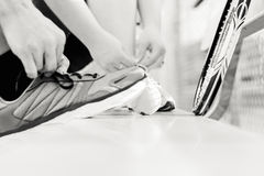 Two People Tying their Shoes before a Game of Tennis Stock Photography