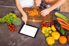 Two people using blank screen tablet in kitchen Royalty Free Stock Images