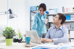Two people using a computer in the office royalty free stock image