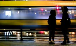 Two people waiting to cross the city street in rainy night. Blurry people waiting to cross the city street in rainy night and a bus passing by royalty free stock photography
