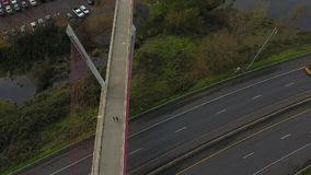 Two People walk across a bride over a freeway stock footage