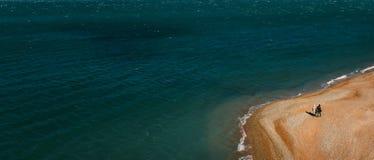 Two people walk along the sea shore, a bird`s eye view. Gelendzhik, Russia Stock Image