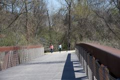 Two People walk a dog over the Wolf River bridge. Royalty Free Stock Image
