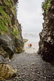 Two people walk onto beach among large rocks Royalty Free Stock Photos