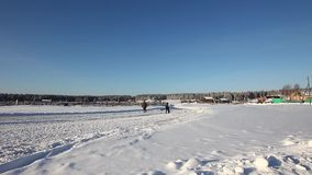 Two people walk on a snowy road in the village. Siberia stock video footage