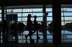 Two people walking at the airport backlit Royalty Free Stock Photos