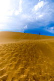 Two people walking along the top of dune. Under cloudy sky Royalty Free Stock Photos