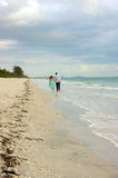 Two people walking away from viewer along beach. In this beach scene there are only two people walking along the shore under cloud filled sky, there are no other Royalty Free Stock Photography