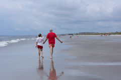 Two people walking on the beach. Girl and a men walking on the beach, turn there backs to the center of the horizontal image. sky is cloudy and big space of sand Stock Images