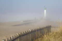 Two people walking on a lighthouse pier on a misty morning Royalty Free Stock Image