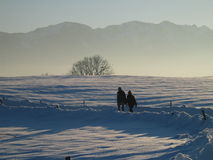 Two People Walking in Lonely Snow and Mountain Landscape Royalty Free Stock Images