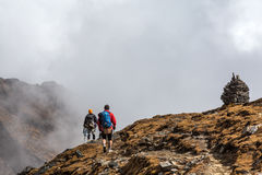 Two People walking on Mountain Slope towards stone Towers Royalty Free Stock Photography