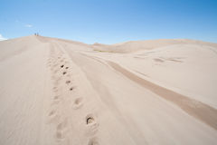 Two People Walking over Sand Dunes. Sand dunes under blue sky at Great Sand Dunes National Park in Colorado Royalty Free Stock Photo
