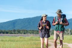 Two people walking on path in meadow field. Male and female traveler looking at attraction view point. Couples adventure at outdo. Ors together. People and royalty free stock photos