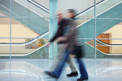 Two People Walking Quickly down Hall in Office Building Royalty Free Stock Photo