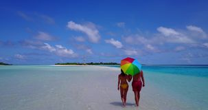 2 people walking romantic young people couple holding hands on a tropical island of white sand beach and blue. Two 2 people walking romantic young people couple stock video