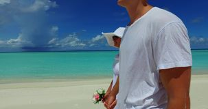 2 people walking romantic young people couple holding hands on a tropical island of white sand beach and blue. Two 2 people walking romantic young people couple stock footage
