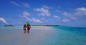 V12646 two 2 people walking romantic young people couple holding hands on a tropical island of white sand beach and blue Stock Photos