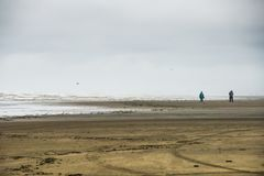Two People Walking On The Sand Beach During Stormy Weather With The Rough Seas and Rolling Wave Beating The Shore. Under a grayish sky in long beach Washington royalty free stock image