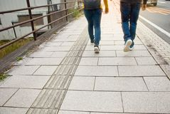 Two people walking on a sidewalk in the morning stock images