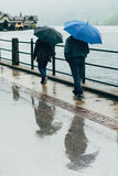 Two people walking in the street on a rainy day stock photos
