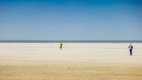 Two people walking  to the sea at a wide beach Stock Photos