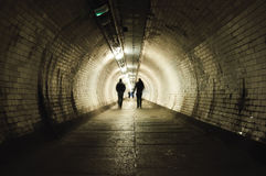Two people walking in the tunnel Stock Image
