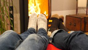 Two people warming their feet by the fireplace. Relaxed scene stock video footage