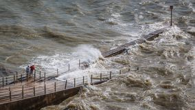Free Two People Watch The Sea From A Jetty Whilst The Wind Causes A Choppy Swell And Waves At High Tide At Royalty Free Stock Image - 159757696