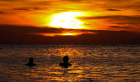 Two people watching sunset. Silhouettes of two people enjoying the sunset within water Stock Photography