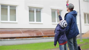 Two people waving. Slow motion. It is a cloudy spring day. They wear warm coats and jeans stock video