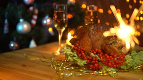 Two people waving sparklers over a festive Christmas table. A man and a woman waving sparklers over a festive table with fried bird and glasses of champagne stock video