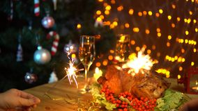 Two people waving sparklers over a festive Christmas table. Two people waving sparklers over a festive table with fried bird and glasses of champagne against the stock video