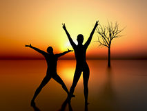 Two people welcoming the sunrise. Digital composition of two people looking at the sunrise as a symbol for happiness, friendship and love Stock Photos