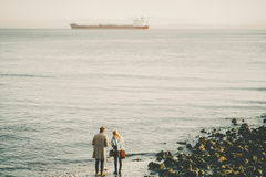 Two people on winter beach and cargo ship in distance Royalty Free Stock Images