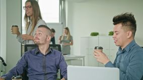Two People are Working on a Laptop. In modern start up office a man brings coffee stock footage