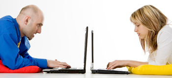Two People Working on Laptops. A man and a woman working on laptops on the floor royalty free stock photography