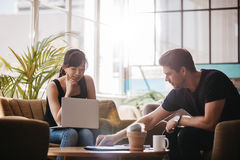 Two people working together in office lobby. Shot of two people sitting in office lobby and working on laptop. Asian women and caucasian men working together in Royalty Free Stock Images