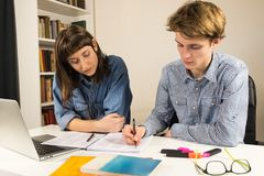 Male and female students or co-workers sitting at table. Two people young men and women do assignment or project together at home office desk Royalty Free Stock Images