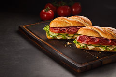 Two pepperoni sandwiches with cheese and cucumber Royalty Free Stock Image